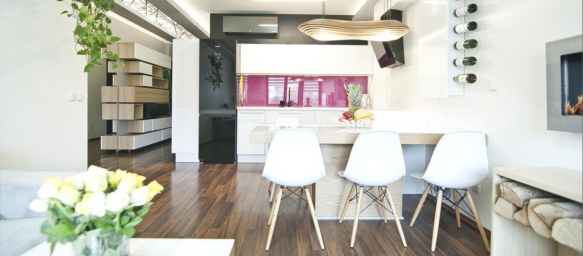 Zdjęcie salonu, na wprost kuchnia i stół kuchenny z krzesłami